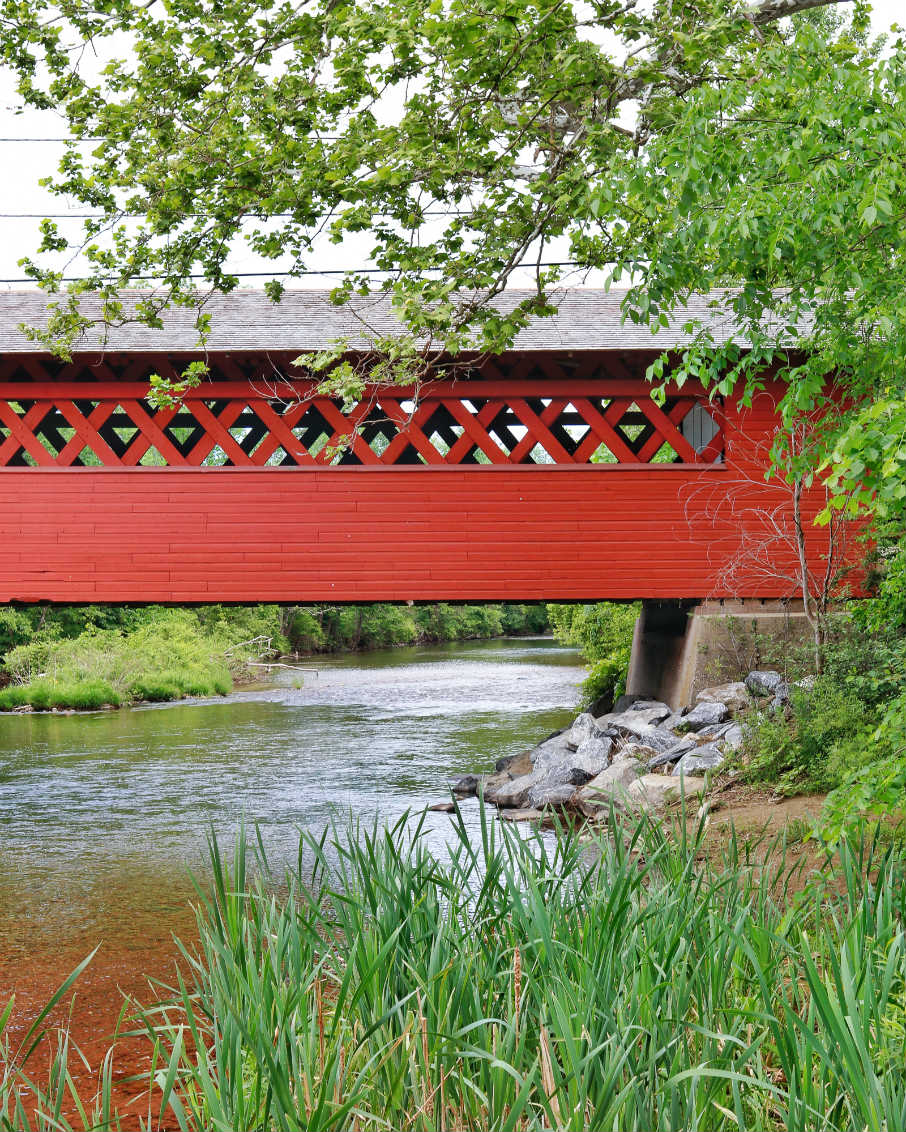red covered bridge vermont river bank