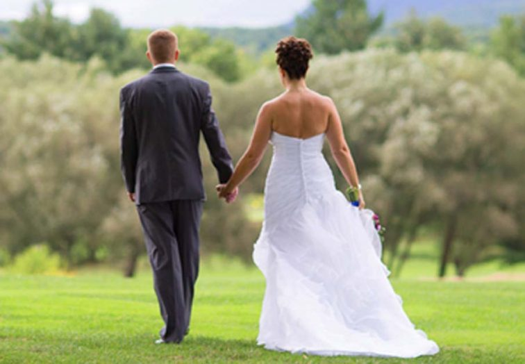 wedding couple in field holding hands