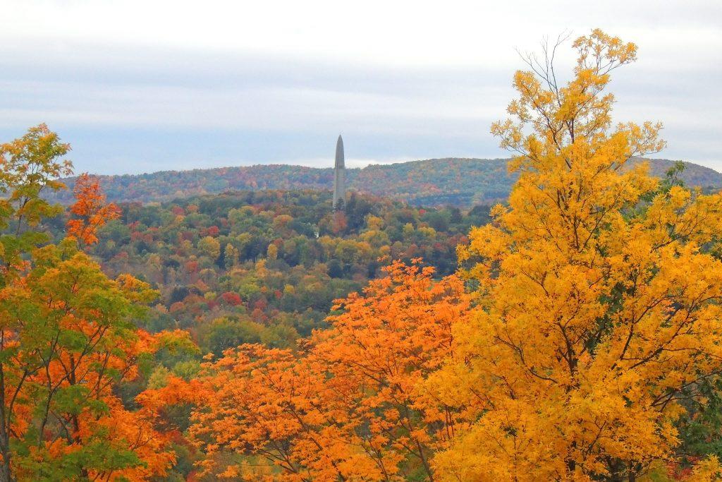 Fall foliage scene in Bennington, VT featuring the Bennington battle monument.