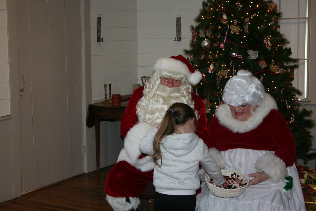 Santa and Mrs. Claus hand out candy to a small child at the Bennington Museum in Bennington, Vermont.