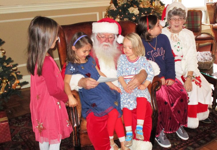 A family celebrates Christmas with Santa and Mrs. Claus