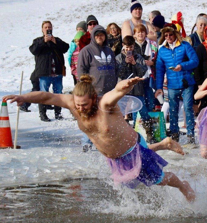 A man jumps into the freezing waters of Lake Paran in North Bennington, VT during the Penguin Plunge.