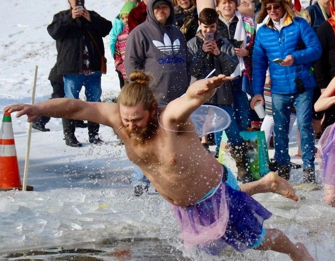 A man jumps into freezing Lake Paran during the Penguin Plunge at Winterfest