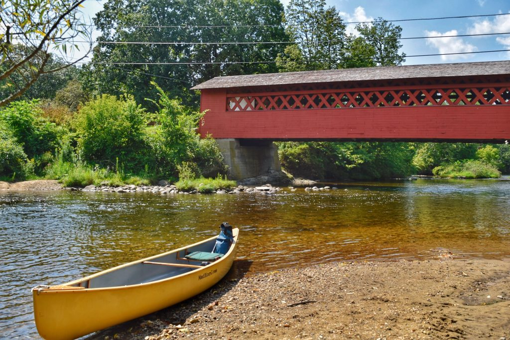 A yellow canoe sits on the bank near the Henry Bridge in North Bennington, Vermont