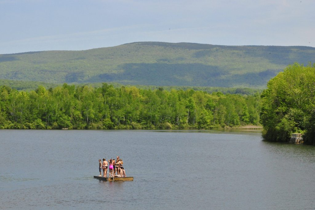 Several kids standing on the floating dock at Lake Paran in North Bennington, Vermont