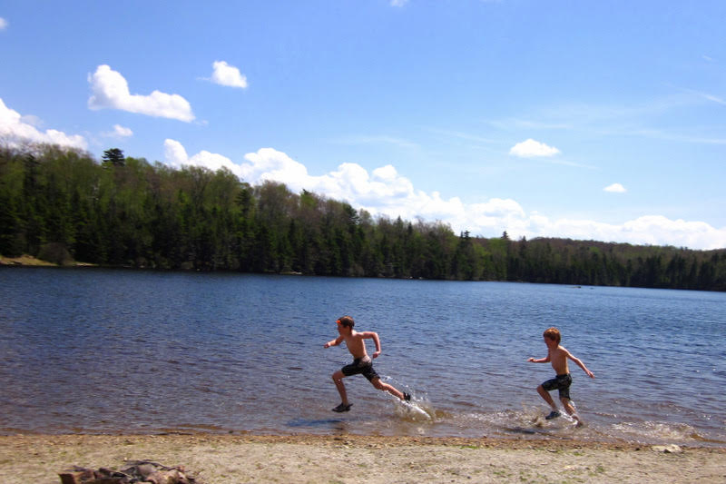Two boys running through the lake at Woodford State Park in Vermont.