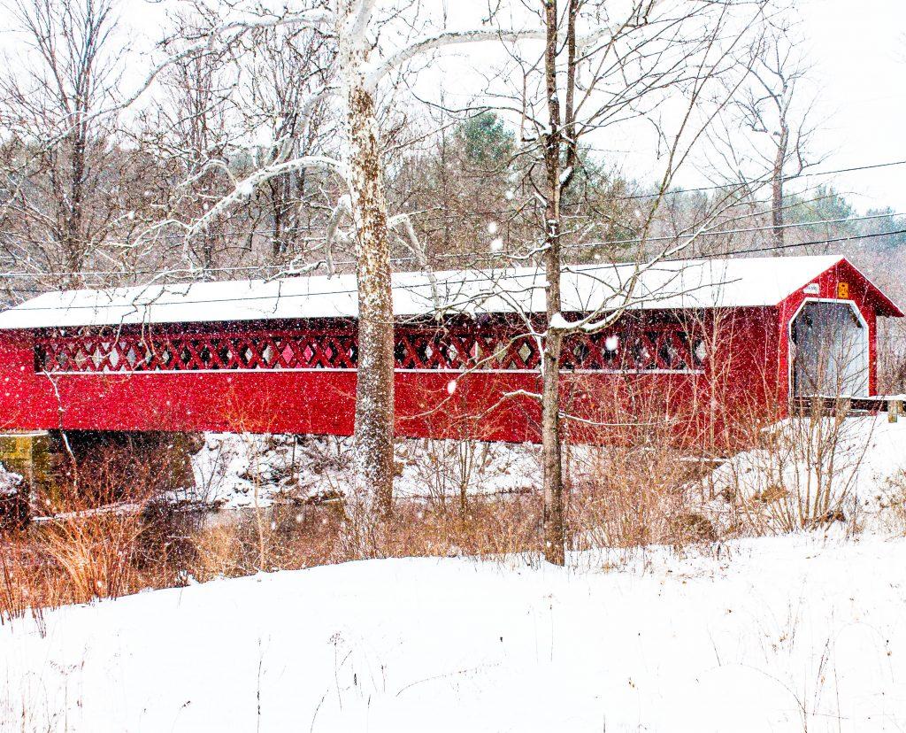 A snowy scene featuring the Burt Henry Covered Bridge in North Bennington, Vermont