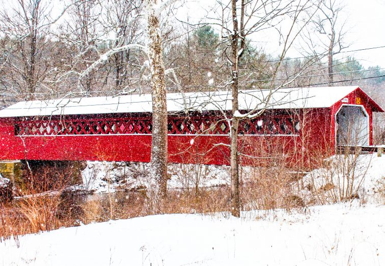 A snowy scene featuring the Burt Henry Covered Bridge in North Bennington, Vermont