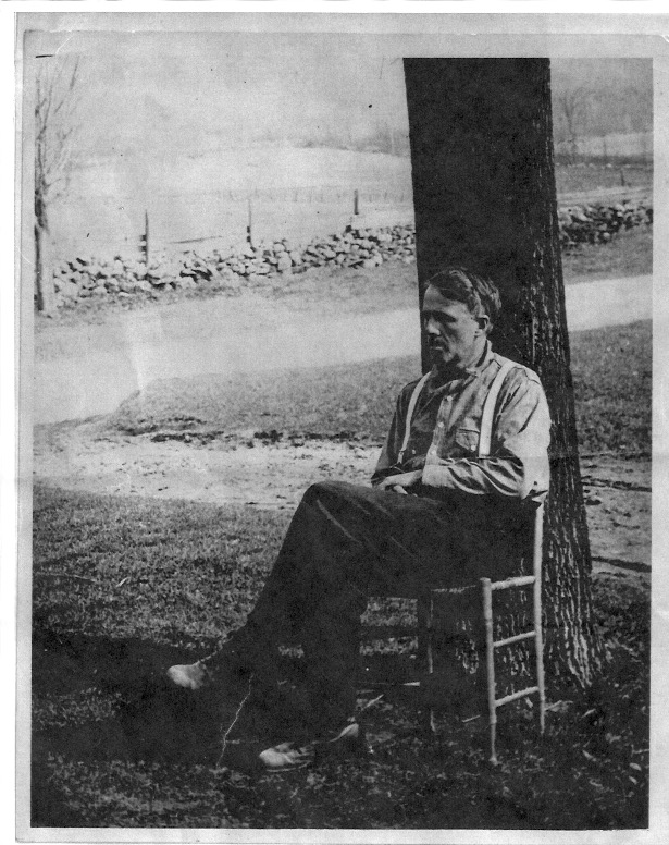 A black and white photo of Robert Frost sitting in a chair under a tree at his home in South Shaftsbury, Vermont.